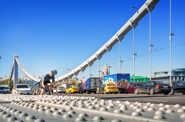 Uitzicht op een verkeersopstopping van auto's en een man in een helm op een fiets op de krim-brug in moskou onder een zomerse blauwe hemel