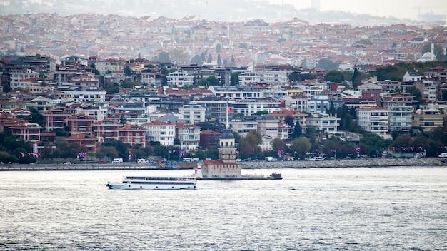 Uitzicht op een wijk met moderne woongebouwen in istanbul, bosporus met leander's toren en bewegende boot op de voorgrond, turkije