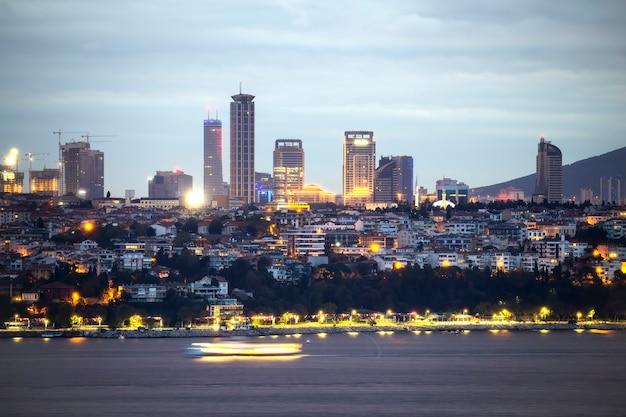 Uitzicht op een wijk met residentiële en hoge moderne gebouwen 's nachts met lange blootstelling in istanbul, bosporus op de voorgrond, turkije
