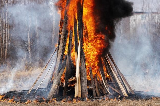 Uitzicht op enorm vreugdevuur van houten planken en autobanden, sterke vlam van rood vuur, zwarte rook in de lucht krullend.