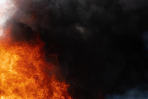 Uitzicht op gevaarlijke rode vlammen van enorm vuur en bewegingswolken van zwarte rook bedekte lucht. defocus, bewegingsonscherpte door sterk vuur en hoge temperaturen door vlammen. atmosferische en rookverspreiding.