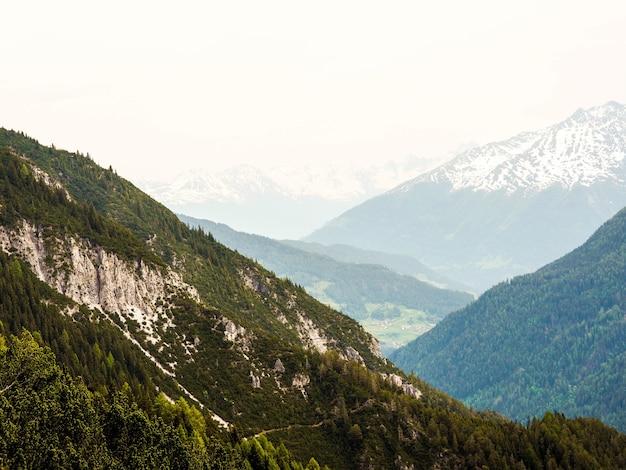 Uitzicht op grote alpine bergen op een mistige dag