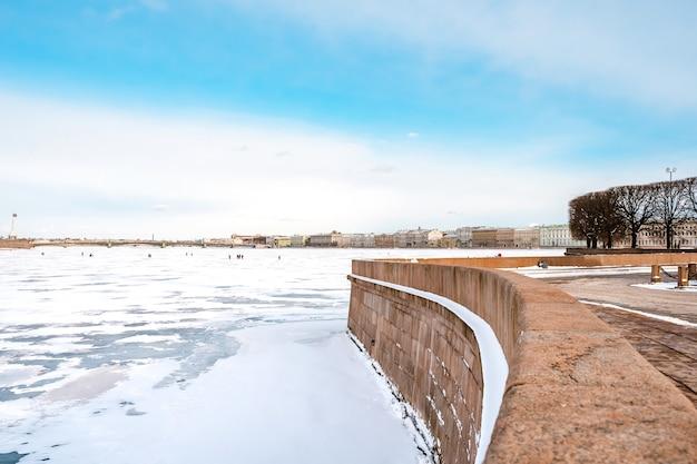 Uitzicht op hermitage (winterpaleis) vanaf de dijk van st. petersburg van de ijzige rivier de neva