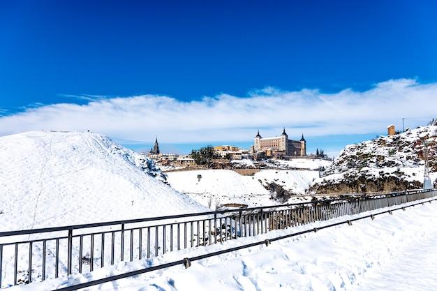 Uitzicht op het alcazar en de stad toledo na de filomena-sneeuwstorm. stedelijk sneeuwlandschap van de stad.