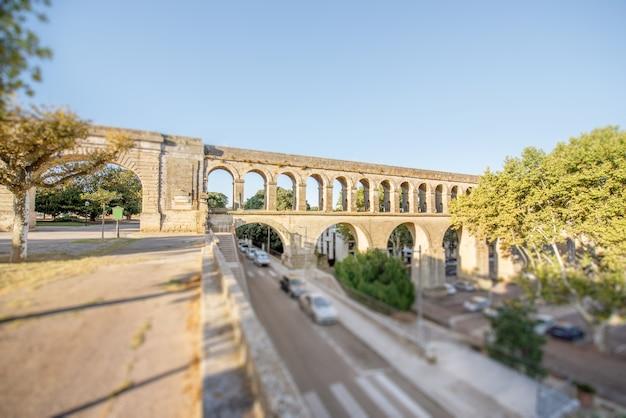 Uitzicht op het aquaduct van heilige clemens in de tuin van peyrou tijdens het ochtendlicht in de stad montpellier in zuid-frankrijk. tilt-shift beeldtechniek met wazige auto's