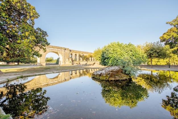 Uitzicht op het aquaduct van heilige clement in de peyrou-tuin met waterreflectie tijdens het ochtendlicht in de stad montpellier in zuid-frankrijk