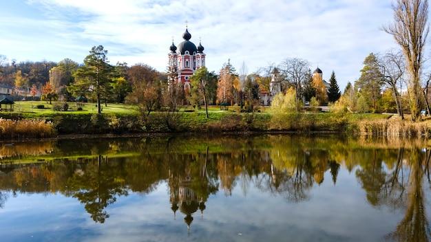 Uitzicht op het curchi-klooster. de kerk en een park. een meer op de voorgrond. moldavië
