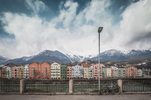 Uitzicht op het historische stadscentrum van innsbruck met kleurrijke huizen langs de rivier de inn en de beroemde oostenrijkse bergtoppen op de achtergrond met een fiets, tirol, oostenrijk