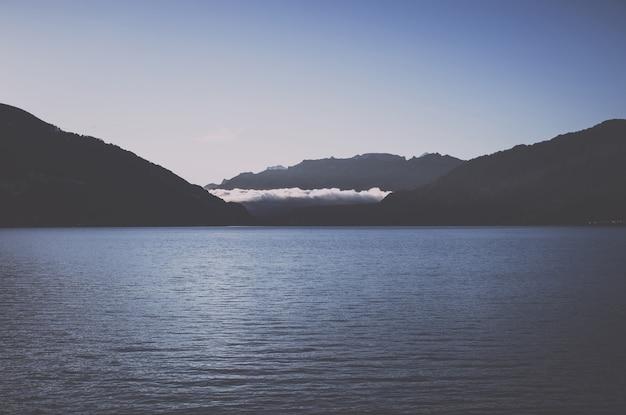 Uitzicht op het meer van thun en de bergen, stad spiez, zwitserland, europa. zomerlandschap, zonneschijn, blauwe lucht en zonnige dag