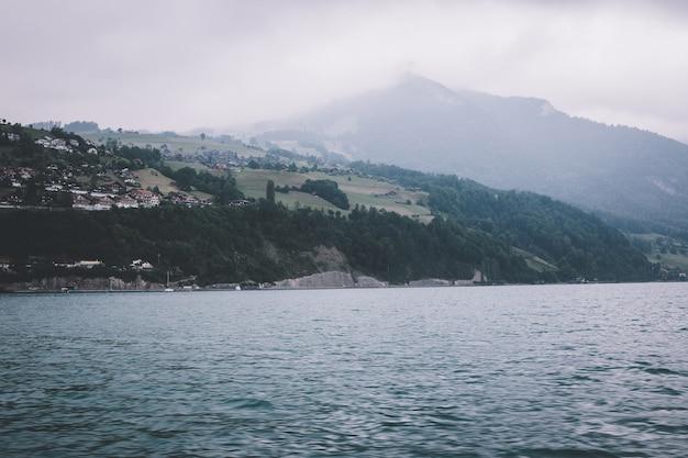 Uitzicht op het meer van thun en de bergen vanaf het schip in de stad spiez, zwitserland, europa. dramatische humeurige blauwe wolkenscène