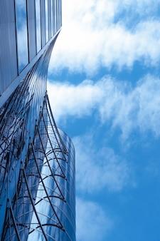 Uitzicht op het moderne gebouw van onderaf met bewolkte blauwe lucht