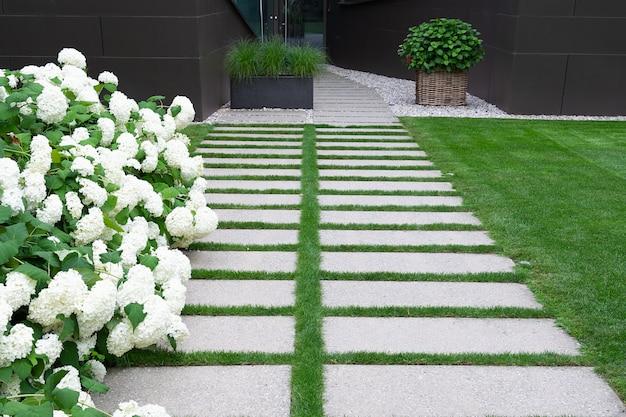 Uitzicht op het pad in de tuin van natuursteen waarlangs het gazon ligt en witte hortensia groeit.