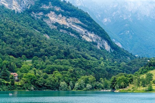 Uitzicht op het prachtige tenno-meer omgeven door groene natuur in trentino, italië