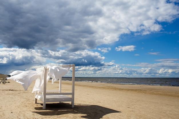 Uitzicht op het prachtige zonnige strandlandschap met bed en witte gordijn op oostzee, blauwe luchtwolken.