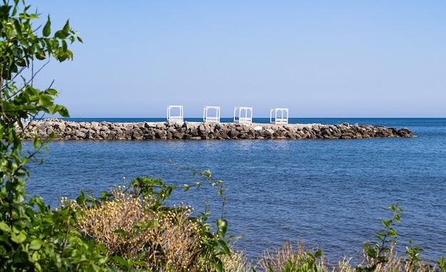 Uitzicht op het stenen strand van de dunne kaap en een kleine baai met enorme rotsblokken.