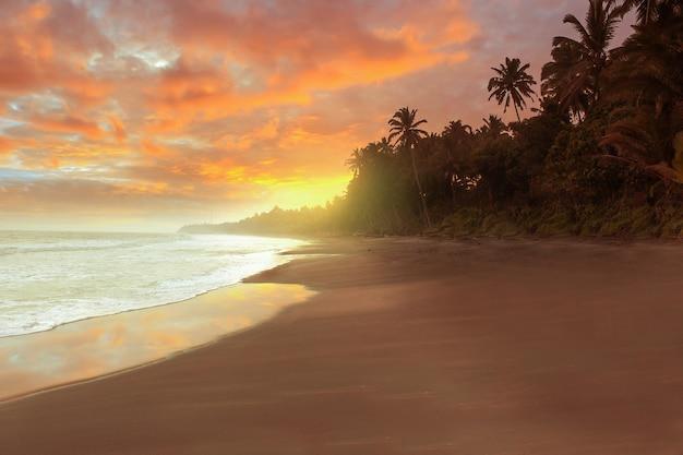 Uitzicht op het strand in de middag met een brandende zonsondergang