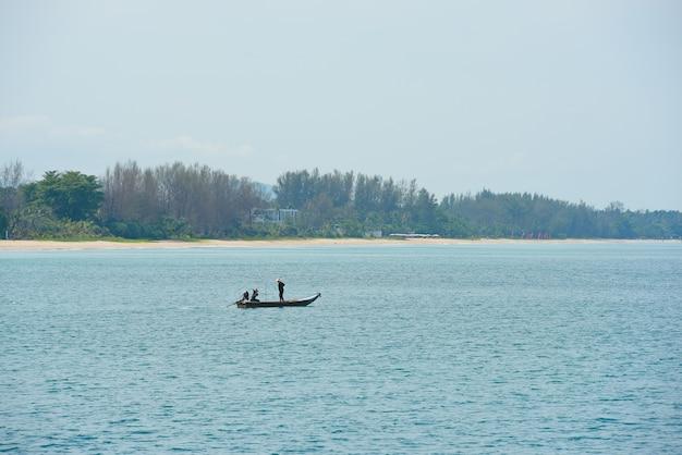 Uitzicht op het strand met pijnbomen en zie het eiland met golven op een zonnige dag