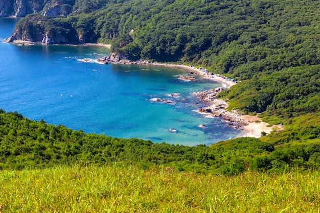 Uitzicht op het strand met turquoise water en groene heuvels in het verre oosten van rusland