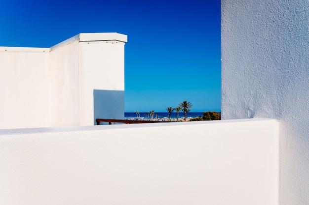 Uitzicht op het strand van de middellandse zee vanaf het dak van een eenvoudig ontworpen appartement met witte muren.
