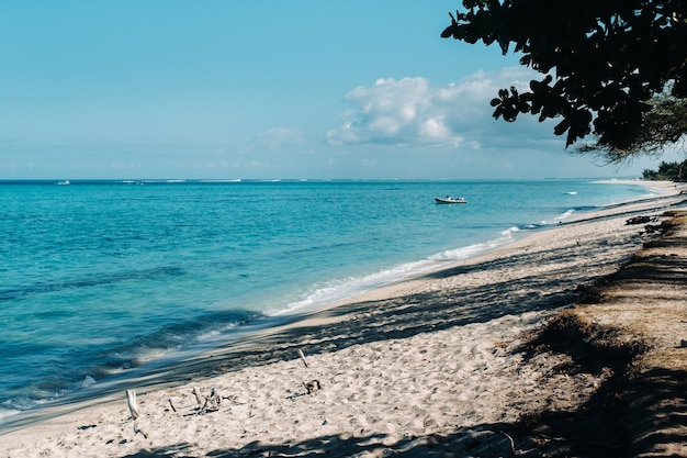 Uitzicht op het witte strand en de turquoise oceaan met een afgemeerde motorboot voor de kust van mauritius