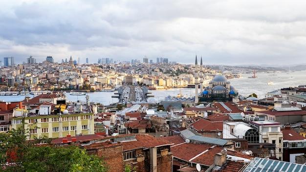 Uitzicht op istanbul bij bewolkt weer, bosporus zeestraat verdelen stad in twee delen, meerdere gebouwen, nieuwe moskee en brug met auto's, turkije