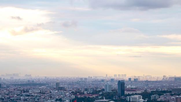 Uitzicht op istanbul bij bewolkt weer, meerdere lage en hoge gebouwen, mist en zonlicht dat door de wolken breekt, turkije
