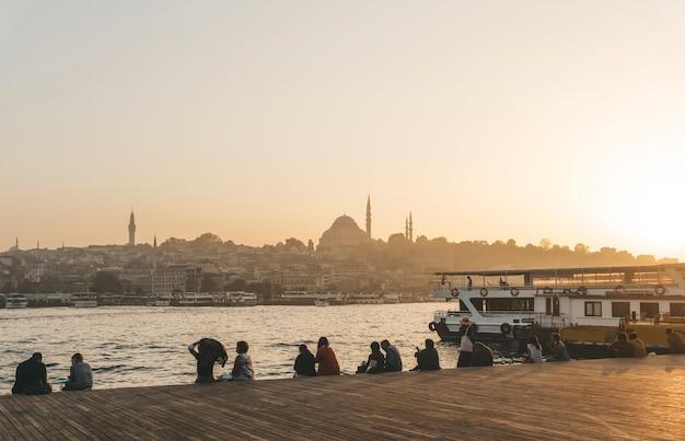 Uitzicht op istanbul vanaf de kade bij zonsondergang. mensen kijken vanaf de pier naar de zonsondergang en het panoramische uitzicht over istanbul