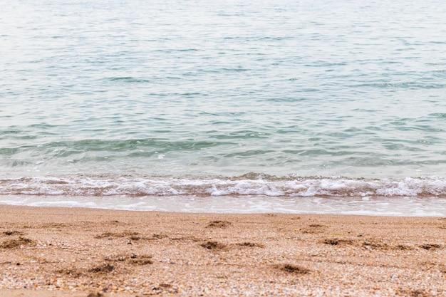 Uitzicht op kalm en helder zeewater en zand