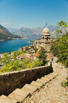 Uitzicht op kerk, oude muren, bergen en zee in de oude stad van kotor. montenegro, baai van kotor. bovenaanzicht