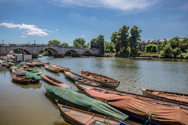 Uitzicht op kleine houten boten in de rivier de theems in de buurt van een oude brug