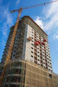 Uitzicht op kraan en bouw bouwplaats tegen blauwe hemel