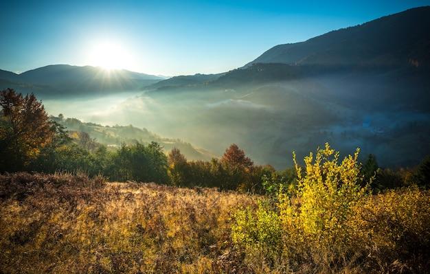 Uitzicht op landschap in heuvelweide met heldere rijzende zon