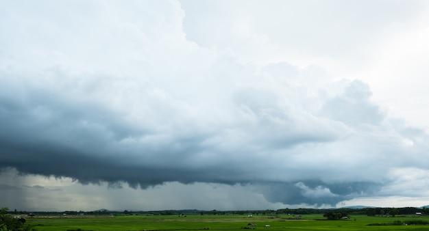 Uitzicht op onweerswolken boven het rijstveld. gietende regen en donkere wolken over het weiland op het platteland.