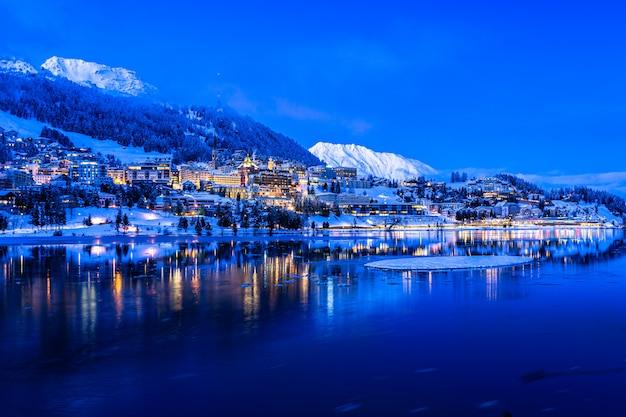 Uitzicht op prachtige nachtlichten van de stad st. moritz in zwitserland 's nachts in de winter, met reflectie van het meer en de sneeuwbergen in backgrouind