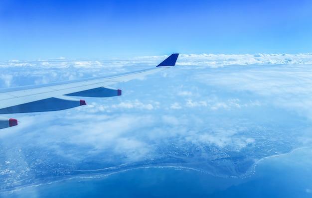 Uitzicht op prachtige wolk en vleugel van het vliegtuig vanuit venster