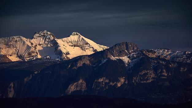 Uitzicht op rotsachtige bergen bedekt met sneeuw tijdens zonsondergang