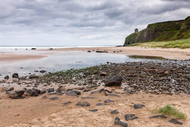 Uitzicht op rotsachtige kust en prieel in downhill demesne, lagen van een inkomend tij en rotsachtig strand op het downhill beach in county londonderry in noord-ierland.
