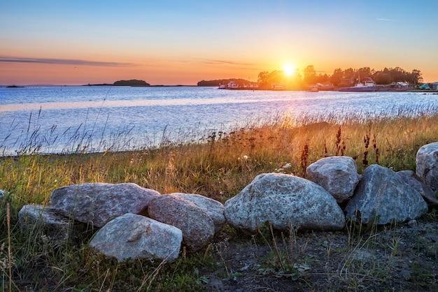 Uitzicht op schepen op de pier en stenen aan de oevers van de solovetsky-eilanden