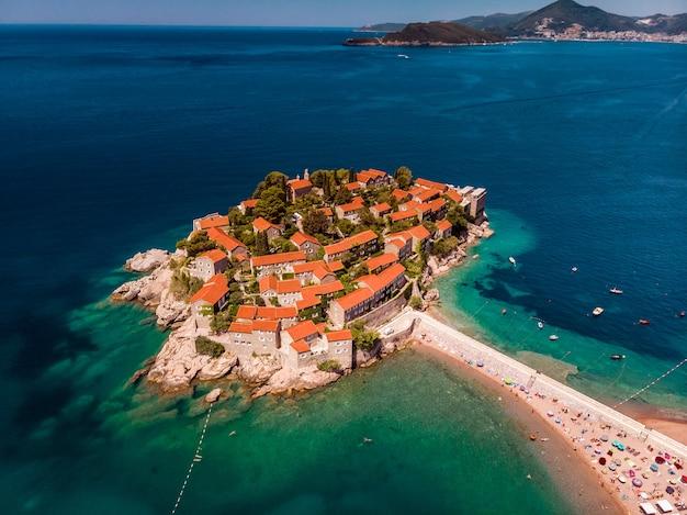 Uitzicht op schoonheid zonsondergang over sveti stefan, klein eilandje en resort in montenegro