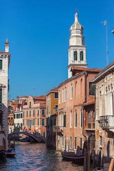 Uitzicht op smal kanaal met boten en gondels in venetië, italië. venetië is een populaire toeristenbestemming van europa