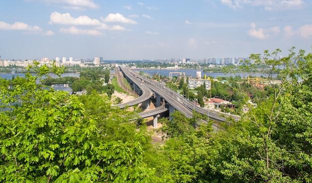 Uitzicht op snelweg- en spoorbruggen vanaf een heuvel over de rivier de dnjepr