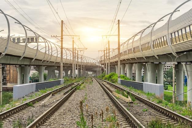 Uitzicht op spoorlijnen en snelweg bruggen bij zonsondergang.