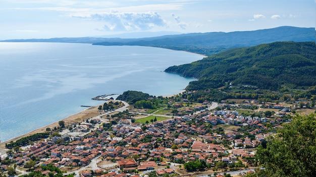 Uitzicht op stratonion vanaf de drone, meerdere gebouwen met rode daken aan de egeïsche zee kosten, heuvels bedekt met groen in griekenland