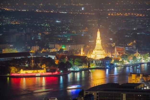 Uitzicht op wat arun en de rivier chao phraya 's nachts