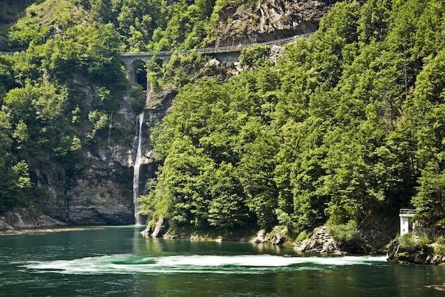 Uitzicht op watervallen met groene bomen in de buurt van het meer