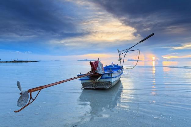 Uitzicht op zee met lange staart boot bij zonsondergang