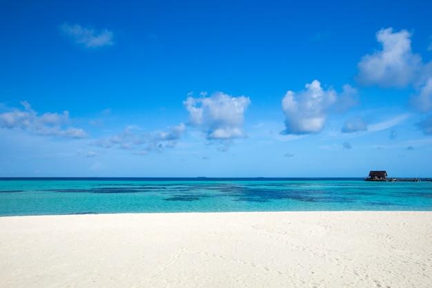 Uitzicht op zee vanaf tropisch strand met zonnige hemel