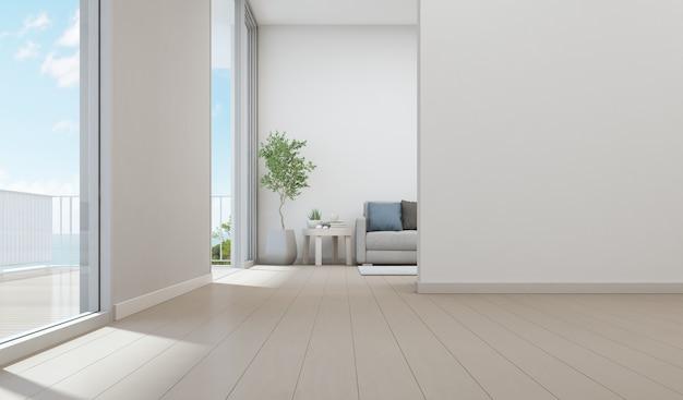 Uitzicht op zee woonkamer van luxe strandhuis met kamerplant in de buurt van glazen deur en houten te