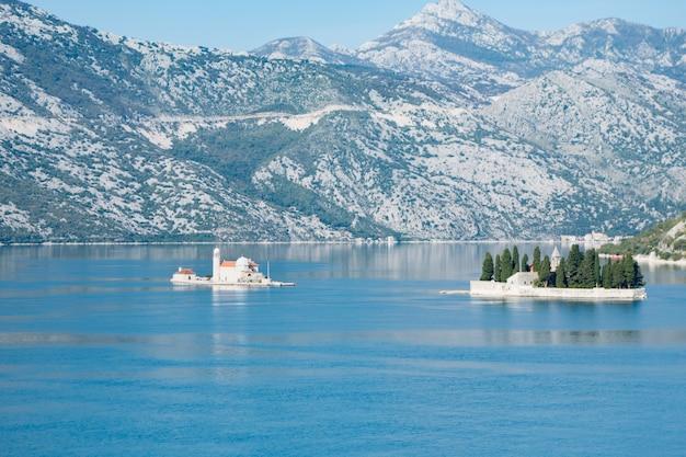 Uitzicht over de baai van kotor omgeven door bergen met de stad perast en het eiland notre dame des roches.
