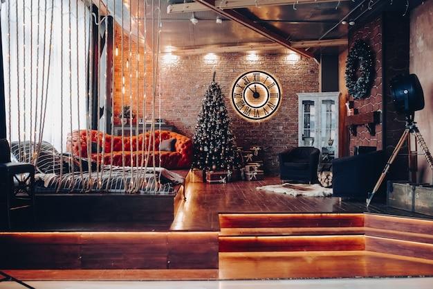 Uitzicht over modern ingerichte kamer voor kerstmis of nieuwjaar. grote klok met romeinse cijfers, rode moderne bank, bed op de grond, twee fauteuils en kerstversiering. loft design interieur.